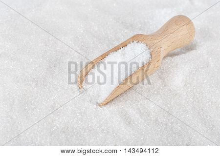 Heap of white sugar with a wooden spoon. White sugar. Wooden scoop on white sugar background