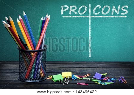 Pro and Cons text on green board and group of pencils