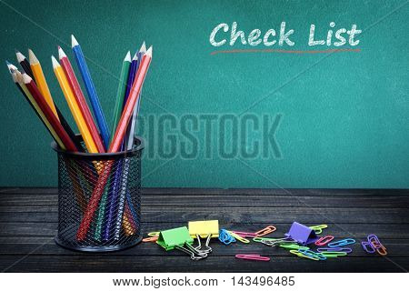 Check list text on green board and group of pencils