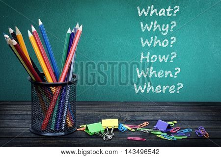 Questions text on green board and group of pencils