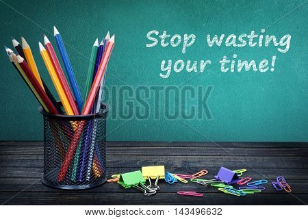 Stop wasting your time text on green board and group of pencils