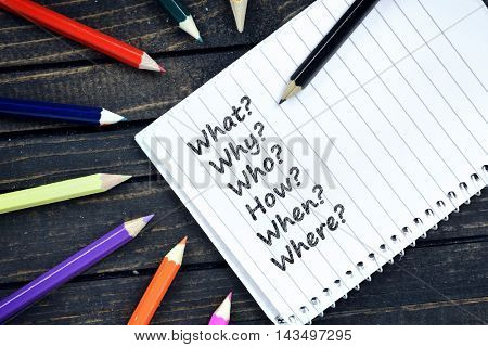 Questions text on notepad and colorful pencils