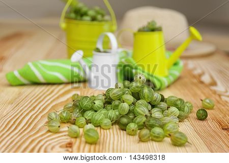 Fresh gooseberries with small watering cans on wooden table