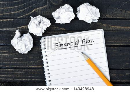 Financial Plan text on notepad and crippled paper