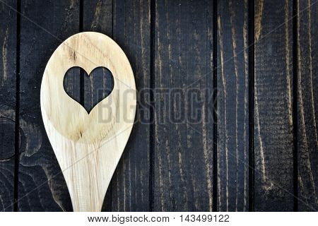 Closeup of spoon with heart shape on wooden table