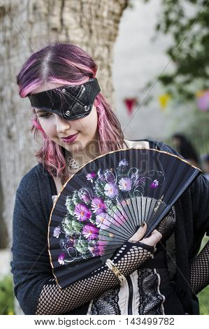 CAGLIARI, ITALY - May 29, 2016: Sunday at La Grande Jatte VIII Ed. At the Public Gardens - Sardinia - portrait of a beautiful young girl with fan and steampunk costumes