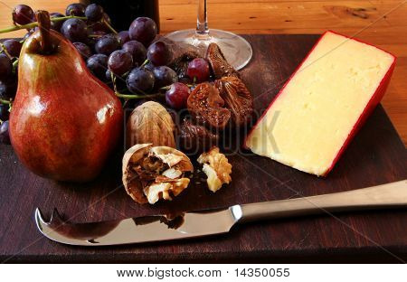 A board with red grapes, walnuts, figs, shiny red pear, sharp cheese, cheese knife, and red wine.