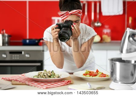 Girl photographing on kitchen. Food blogger concept