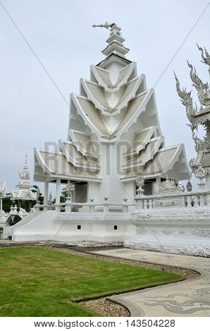 The Buddhist Wat Rong Khun or white temple in Chiang Rai Thailand on an overcast day.