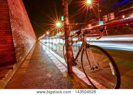 Bicycles parked in the street with lights at night in Tha pae  gate, Chiang Mai, Thailand.
