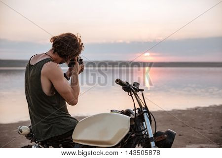 Young man making photo with camera while sitting on his motocycle outdoors