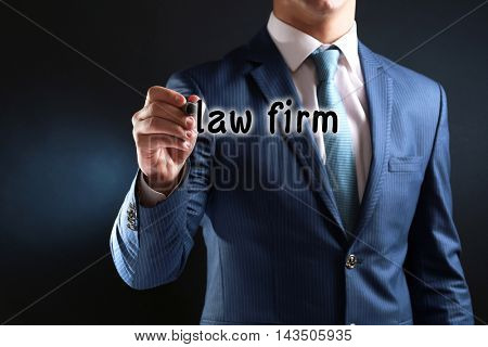 Businessman in suit with pen on dark background. Law firm