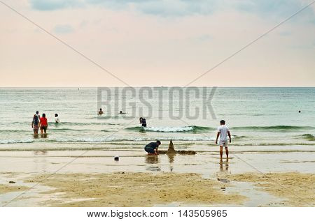 KOH CHANG, THAILAND- APRIL 12, 2015: Thais and tourists resting on the White sand beach of Chang island before sunset. Koh Chang is a famous tourist destination in Thailand