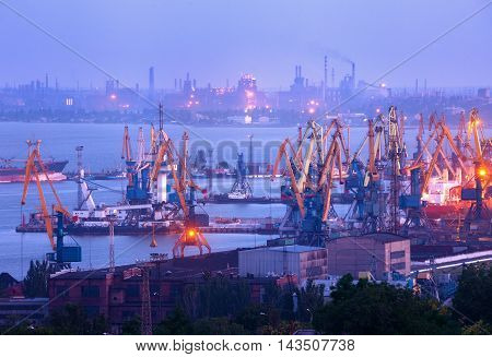 Sea Commercial Port At Night Against Working Steel Plant