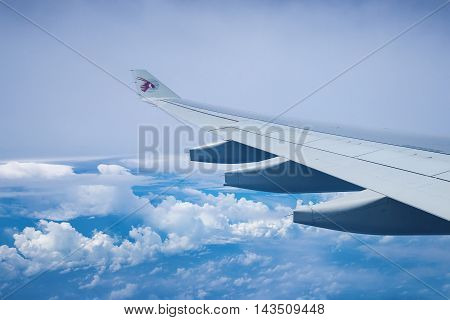 DOHA QATAR - JUNE 9 2016: A view of the airplane wing as seen through window of an aircraft Qatar Airways. Qatar Airways is included in the list of seven airlines with the highest five-star rating under the version of the British agency Skytrax.