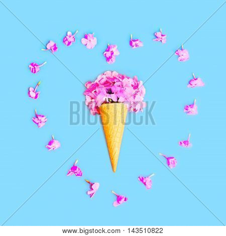Heart Shape Of Petals With Ice Cream Cone With Flowers Over Colorful Blue Background