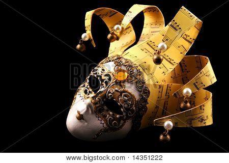 Golden Venetian mask, isolated on black background.