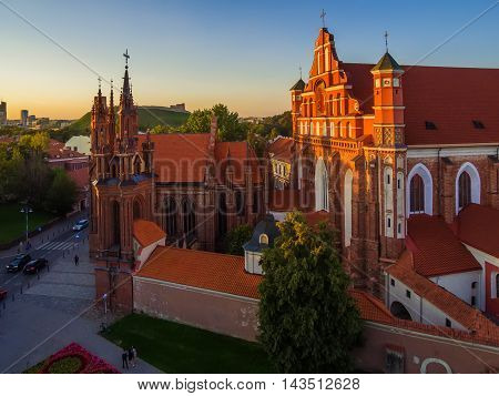 AERIAL. Old Town in Vilnius, Lithuania: St Anne's and Bernadine's Churches, Lithuanian: Sv. Onos ir Bernardinu baznycios. Representative summer picture