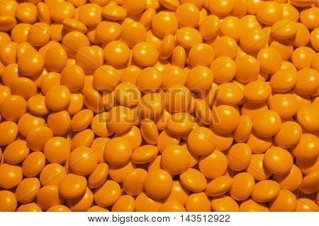 A scattering of yellow pills. The possibility of addiction to the medication and excess dosage.