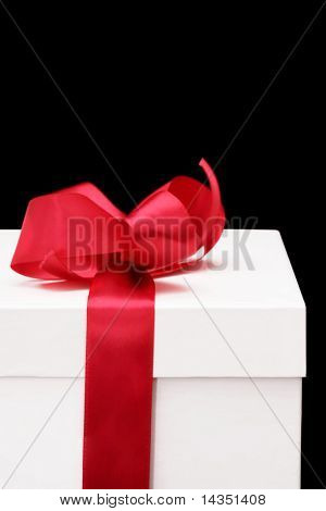 Caixa de presente branco com fita de cetim vermelha.  Fundo preto.