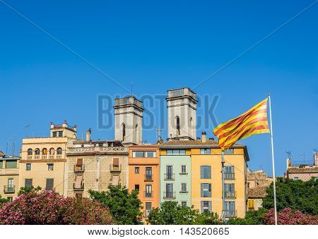 Flag of Catalonia called Senyera waving in the downtown of Girona with bell towers of Anunciacion convent in background. Gerona Costa Brava Catalonia Spain.