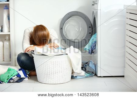 tired unhappy woman housewife is engaged in the laundry fold clothes into the washing machine