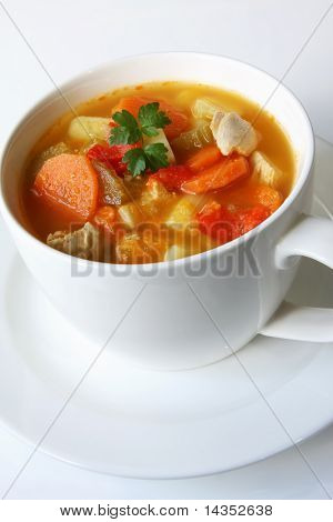 Home-made chicken and vegetable soup, in a white soup cup.