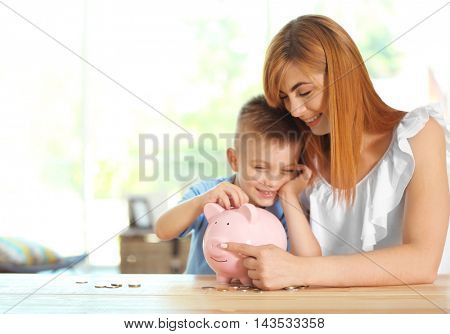 Savings concept. Mother and little boy putting coins into piggy bank