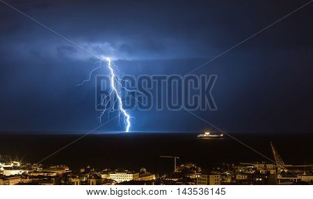 Massive cloud to ground lightning bolts hitting the horizon of city lights