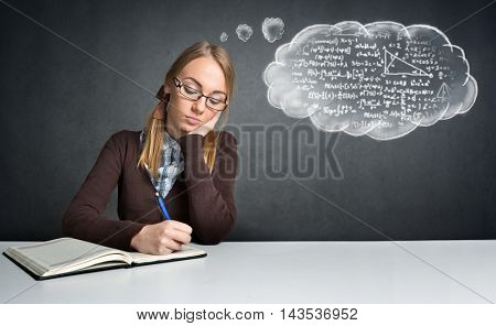 Thinking  student sitting at a desk and working math homework
