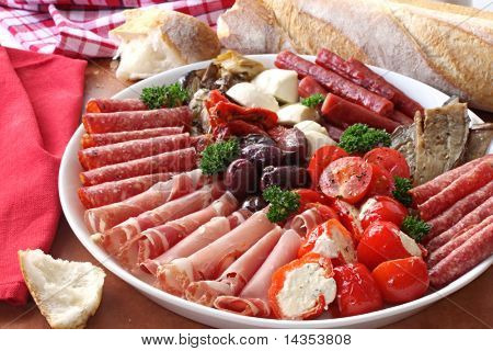 Platter of antipasto, with crusty bread.  A mixture of salami, prosciutto, bocconcini, grilled peppers stuffed with goat's cheese, eggplant, tomatoes, and olives.
