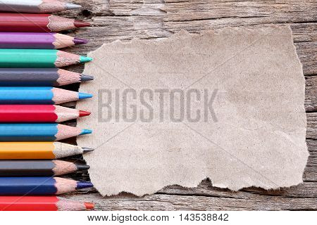 Colored pencils or Crayons and brown cardboard on old wooden floor concepts about education.