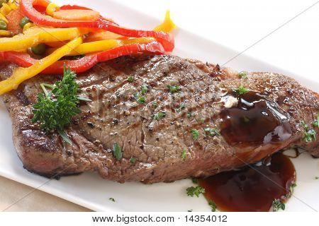 Grilled strip or porterhouse grain-fed beef steak, with colorful vegetables and an onion gravy.