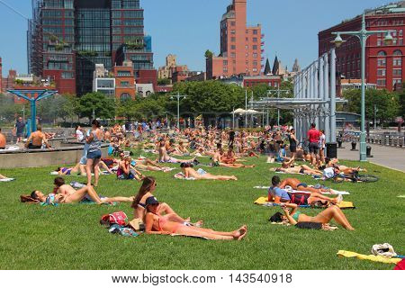 new york city, new york, june 2016; In this photo we see people, sunbathing at the christopher street pier, in the west village. new york city, new york, june 2016.