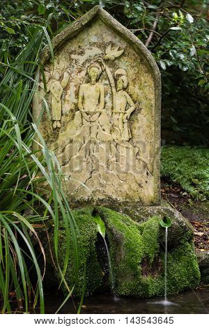 Stone of Holy well at St. Mary's Church, Charlcombe. Quiet garden in churchyard near Bath Somerset UK with stone by well fed by spring water famed for its healing properties