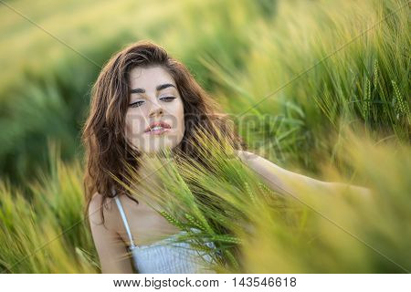 Dazzling smiling girl sits in the rye field and looks down. She wears a light dress. Sunlight fills from the back. Outdoors. Horizontal.