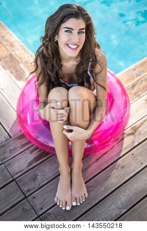 Dazzling girl in a white swimsuit sits on the pink rubber ring and looks into the camera with a smile on the background of the swimming pool. She hugs her legs with her hands. Vertical.