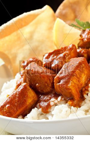 Butter chicken over rice, with poppadoms.  Delicious Indian food. poster