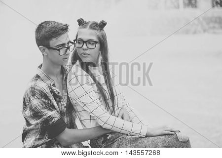 Loving couple teenagers embrace. Girlfriend and boyfriend hugging. They wear glasses. Black and white photography. First love. He falls in love. Date.