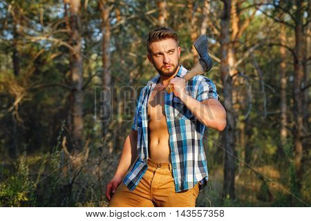 Lumberjack with an ax posing. Woodcutter in unbuttoned shirt in the coniferous forest. Felling trees. Logging. Manual labor. Brutal man.