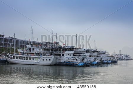 Halong Bay, Vietnam - Dec 12, 2015: White tourist boats moored in Halong Bay in the Winter morning sunshine.