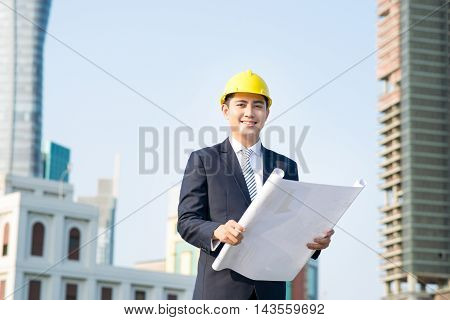 Architect holding blueprints and looking at the building at the construction