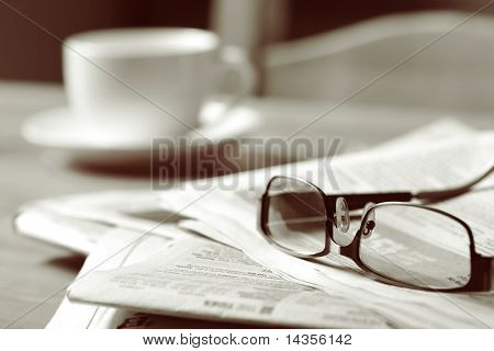Newspapers and coffee cup, with reading glasses.  Toned image, focus on reading glasses.