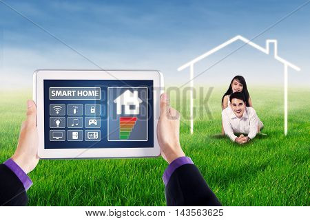 Close up of smart home controller system on the tablet with happy couple lying on the meadow under a house symbol