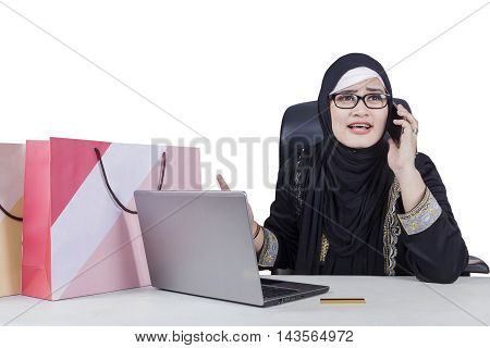 Muslim woman looks disappointed after shopping online and complaining by phone with laptop and shopping bags on the table