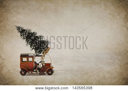Old metal tin toy car with a christmas tree on the roof. Christmas decoration for a greeting card or concept for shopping.
