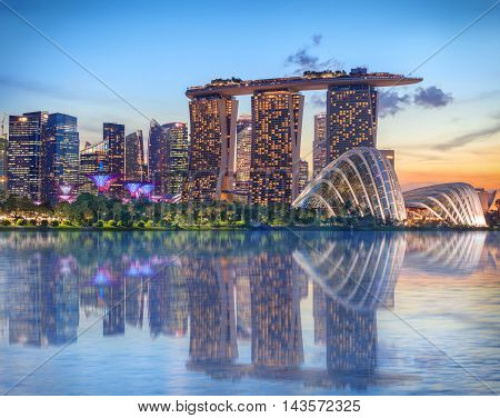 Singapore, Republic of Singapore - May 4, 2016: Supertree grove, Cloud garden greenhouse and Marina Bay Sands hotel reflecting in water at dusk with glowing lights