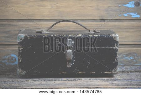 Old and dirty wooden suitcase on table