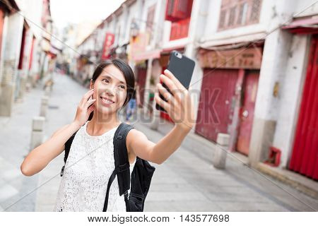 Woman taking selfie by camera in Macao city