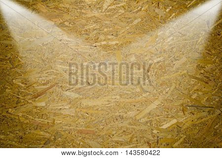 Oriented Strand Board. Building material. Wooden panel made of pressed sandy brown wood shavings as background closeup by two lights